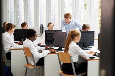 Students in blue and white uniforms sitting at computers in a classroom with teacher looking on