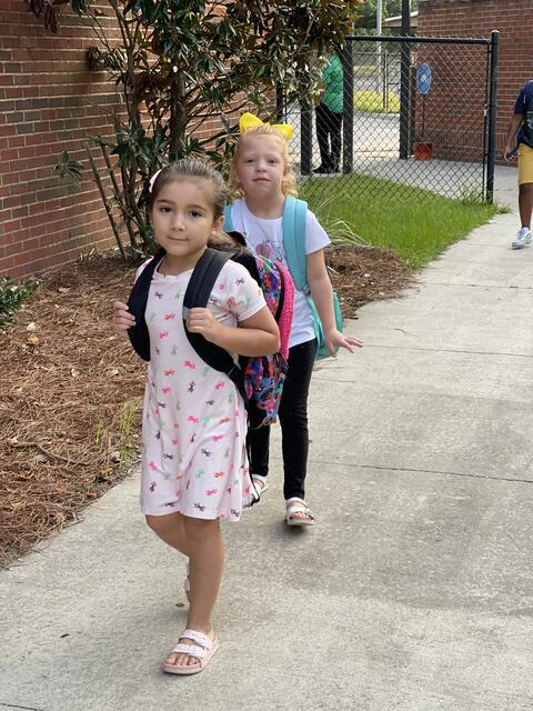 Candid photo: Two girls with backpacks walking in to school.