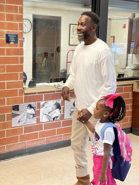 Grandfather walking granddaughter in to school.