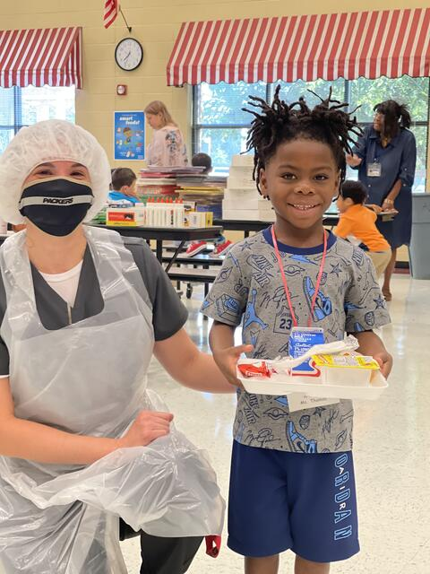 Candid photo: School nutrition worker with student holding a breakfast meal tray.