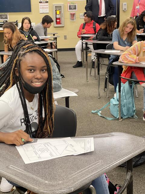 Candid photo: Student working at her desk with other students in the background.