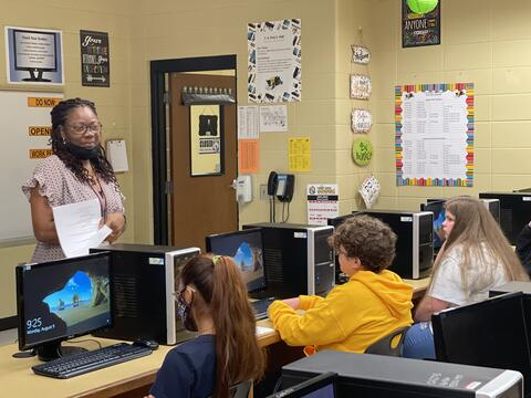 Candid photo: Teacher with students in a computer lab