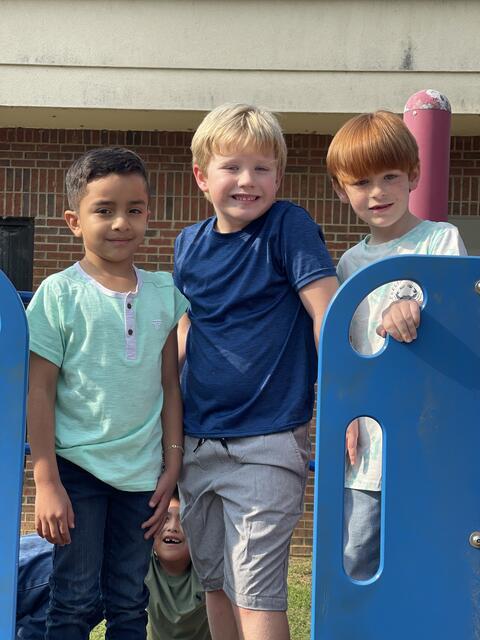 Candid photo: Three elementary boys on playground equipment.