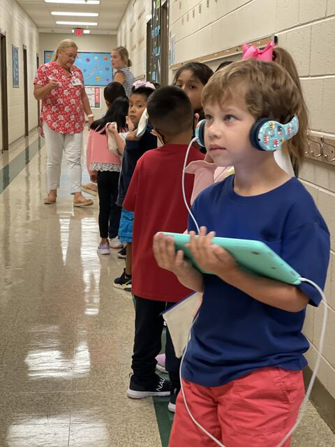 Candid photo: Student with headphones and an ipad lined up in the hallway with other students.
