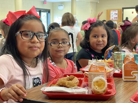 Candid photo: Three elementary girls at lunch with lunch trays.