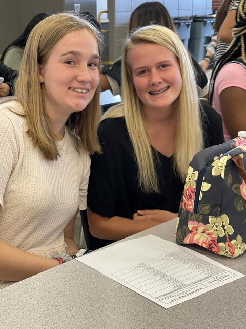 Candid photo:  Two high school girls at a table with bookbags.