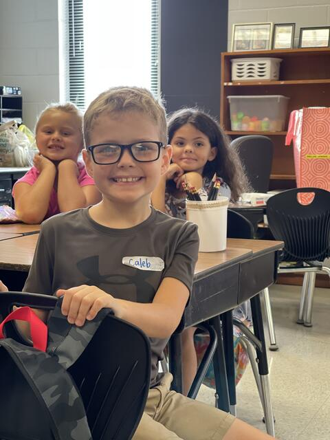 Candid Photo: Three students, one boy and two girls in the background in a classroom.