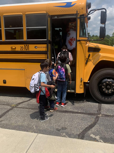 Candid Photo: Students loading a bus to go home.