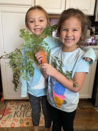 Picture of two girls holding a carrot from their garden.