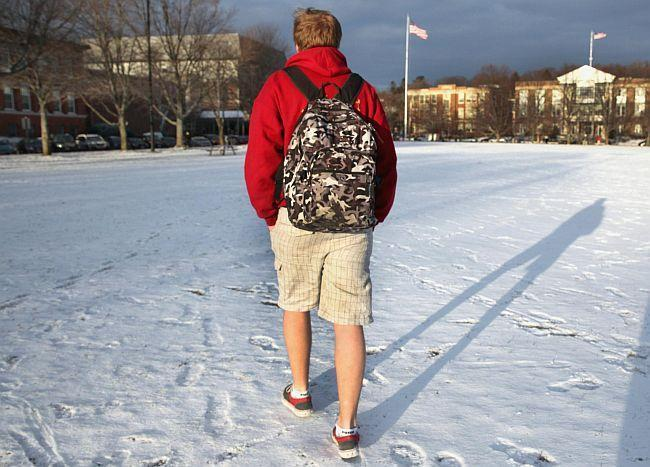 Student with backpack walking across campus in snow