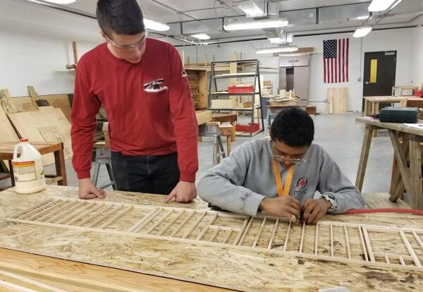 Older PTEC student mentoring a younger student.