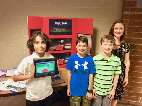 Students displaying project with Teacher