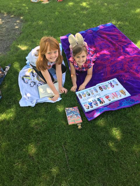 Girls with book on lawn