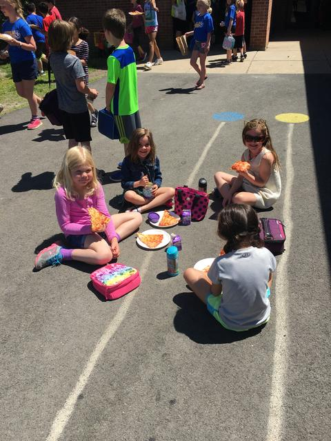 Girls seated, eating lunch on track