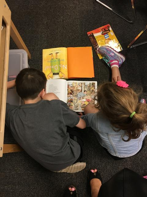 Rear view of 2 students sharing a book