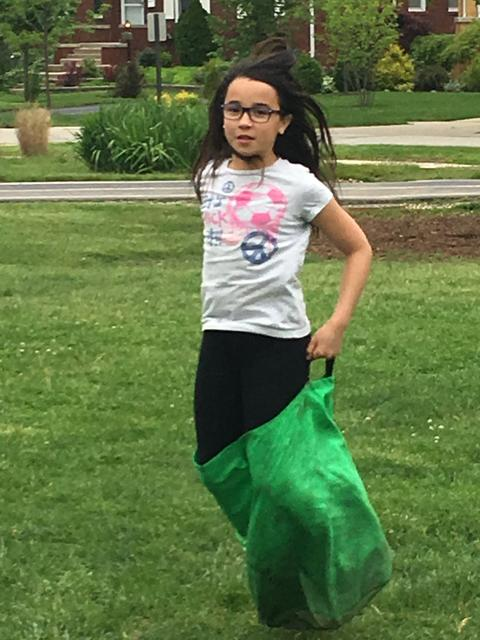 Girl holding up sack waiting for race
