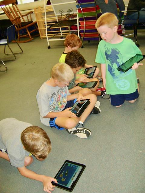 Group of boys on floor with iPads