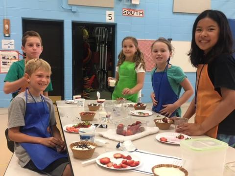 Group of students creating strawberry treat