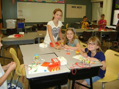 Three girls wiring with playdough