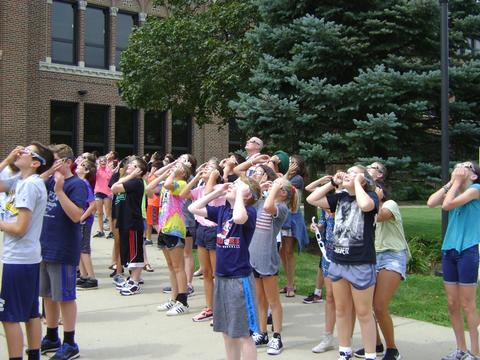 Students on school sidewalk viewing eclipse