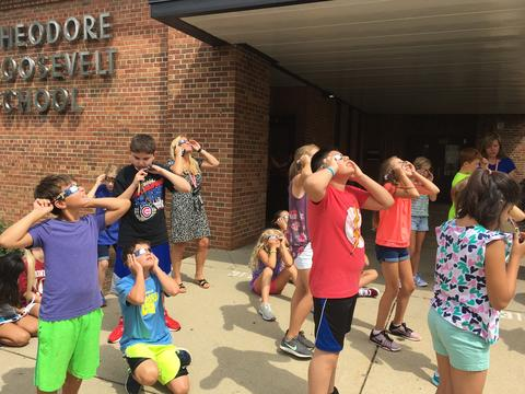 Students adjusting glasses for eclipse viewing