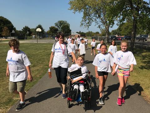 Boy in wheelchair participating in walk