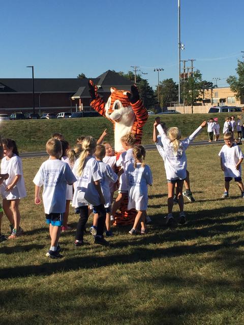 Children surrounding Tiger mascot