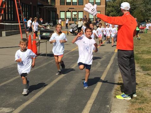 Students running past the Principal