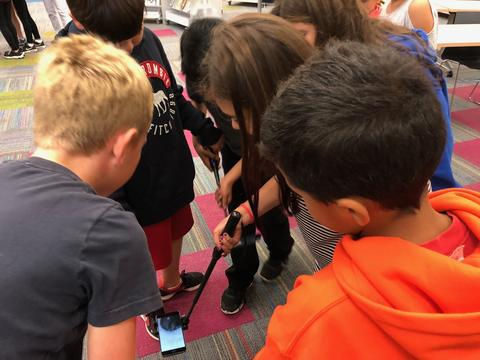 students huddled around an augmented reality item find