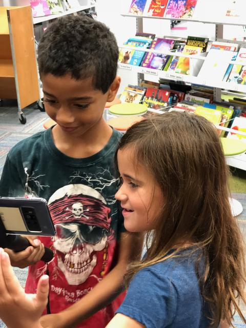 close up of two students discovering an AR item