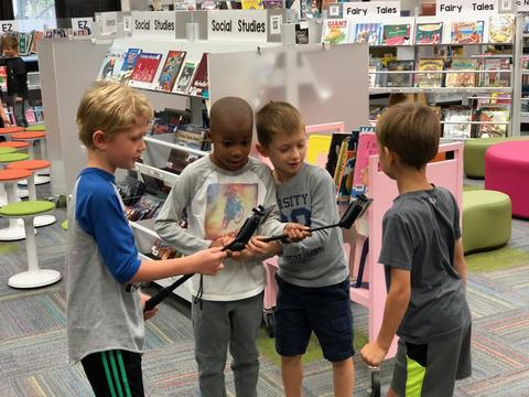 four boys sharing their item