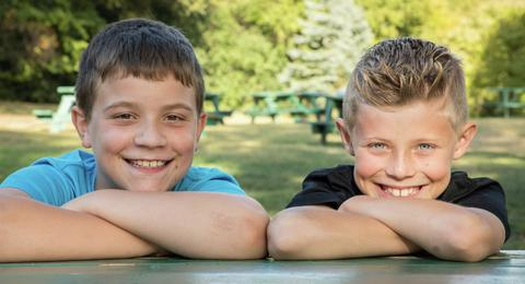 two boys with heads leaning on folded hands posing for camera