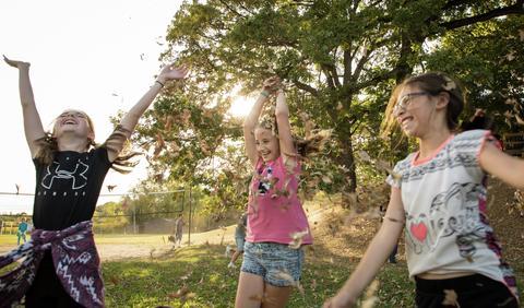 three girls throwing up leaves