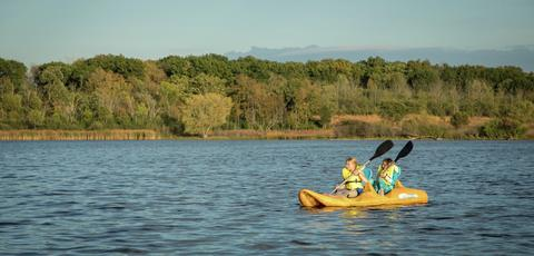 two students rowing a boat out in the water