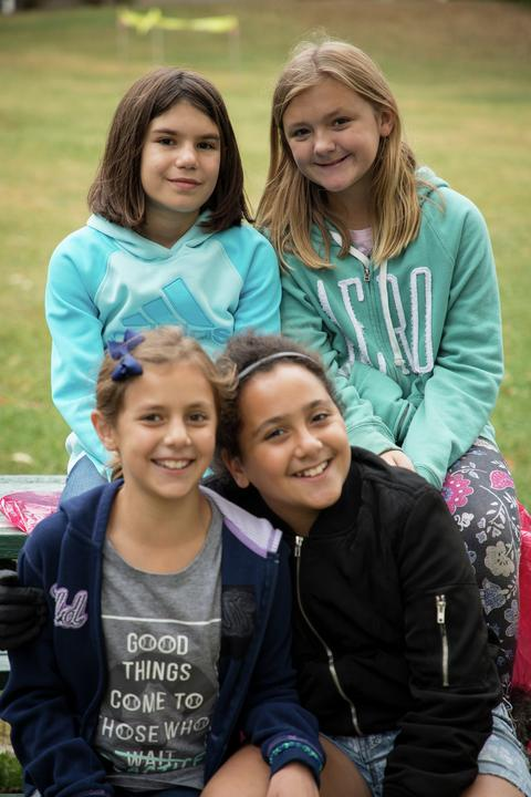 four girls sitting on picnic table
