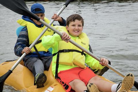 boys crossing oars in a row boat