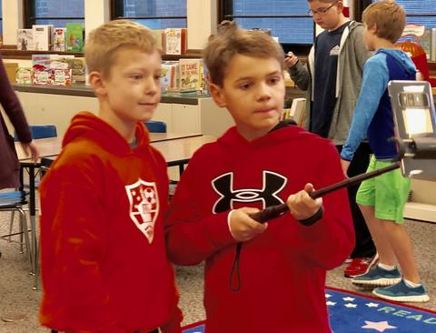 two boys looking at device