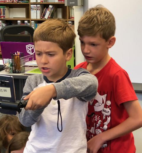 Two boys manipulating the selfie stick to find images
