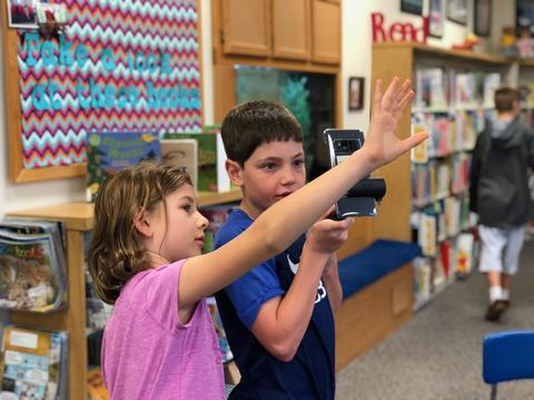 two students holding up device to see images over head