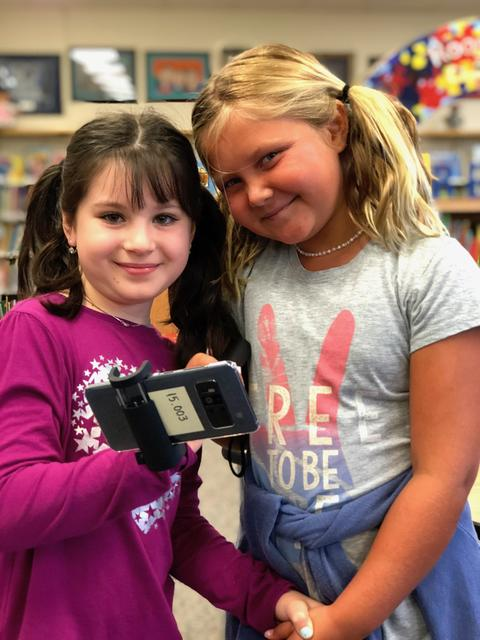 Two girls smiling for camera with device