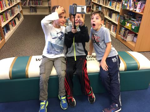 Three boys excitedly view image