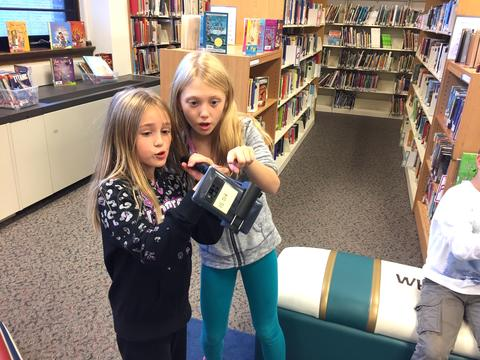 one girl pointing out something on device to another