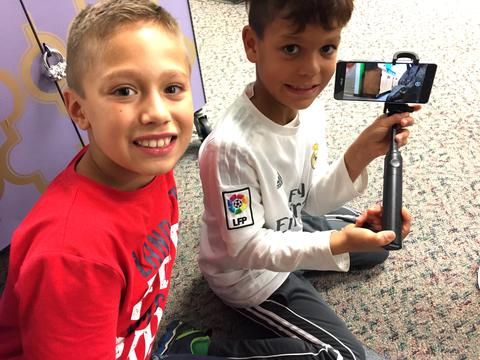 Two boys display their screen with image
