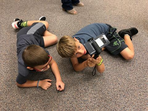 two boys on the floor looking up at the device