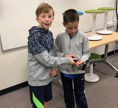 two students sharing the device handling
