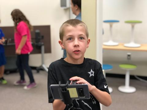 boy with device extended, smiling for a picture