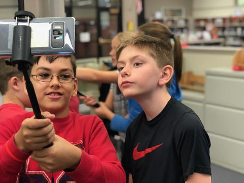 two students holding device high to get a view of an image
