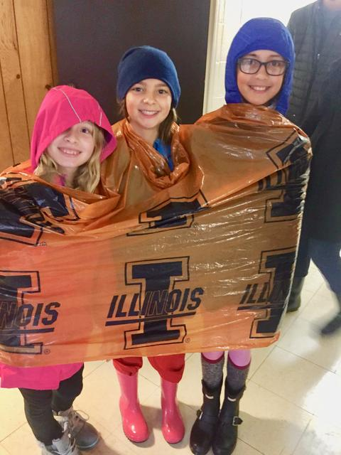 Three girls with hoods up and encased in plastic for rain prevention