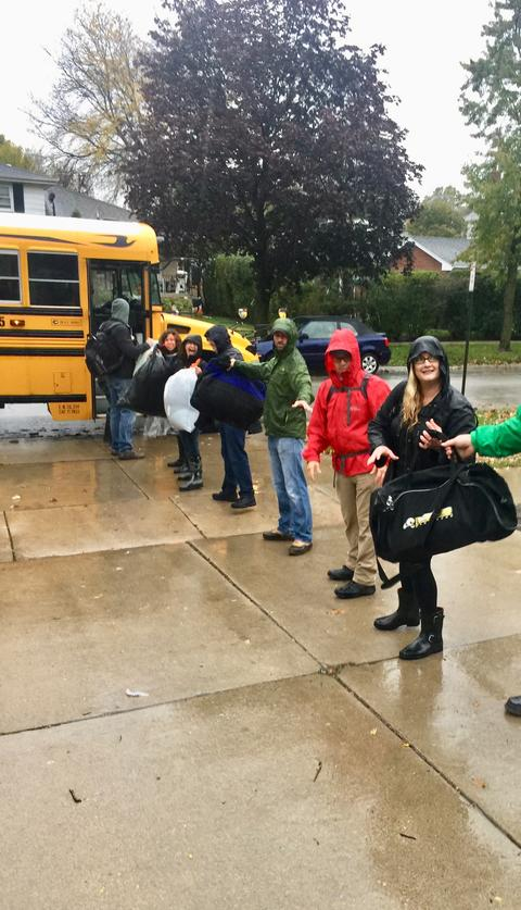 Students lined up loading bags onto the bus