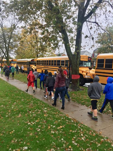 Students filing to buses to leave for camp duncan